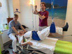 Foto vom Schlingentisch: Ein Therapeut wurde mit Seilen aufgehängt, ein Therapeut massiert den Nacken und einer verstellt die Seile